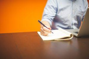 אדם יושב מול מחשב ולידו נייר שעליו הוא כותב