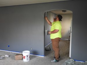 אדם צובע קיר גבס שנבנה בתוך דירה